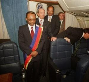 L'ex-président Jean-Bertrand Aristide dans l'avion du retour flanqué de Warren Christopher