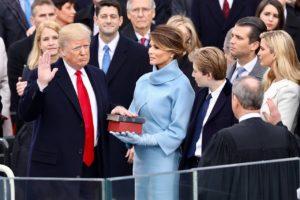 Trump prêtant serment le jour de son inauguration: main gauche sur deux Bibles, celle de Lincoln et celle de la famille tenues par son épouse Melania.