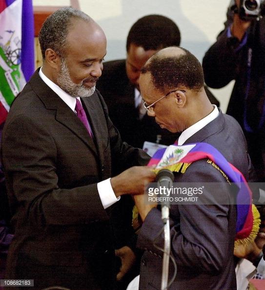 René Préval remettant l'écharpe présidentielle à Jean-Bertrand Aristide