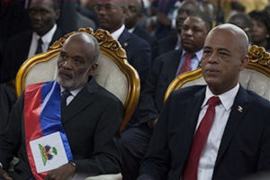 "On May 14, 2011, President Préval prepares to pass the presidential sash to his successor Michel Martelly, who won power through an ""electoral coup d'état."""