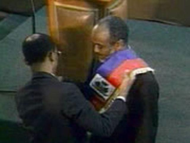 Jean-Bertrand Aristide passant l'écharpe présidentielle à René Préval
